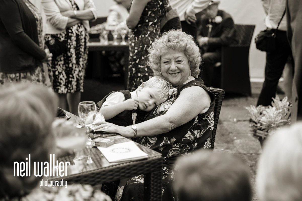 mother of the groom hugging a page boy