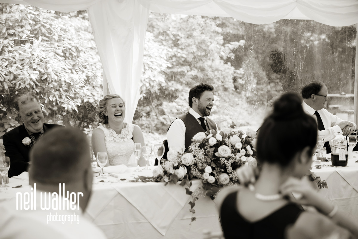 bride & groom laughing at the best man's speech