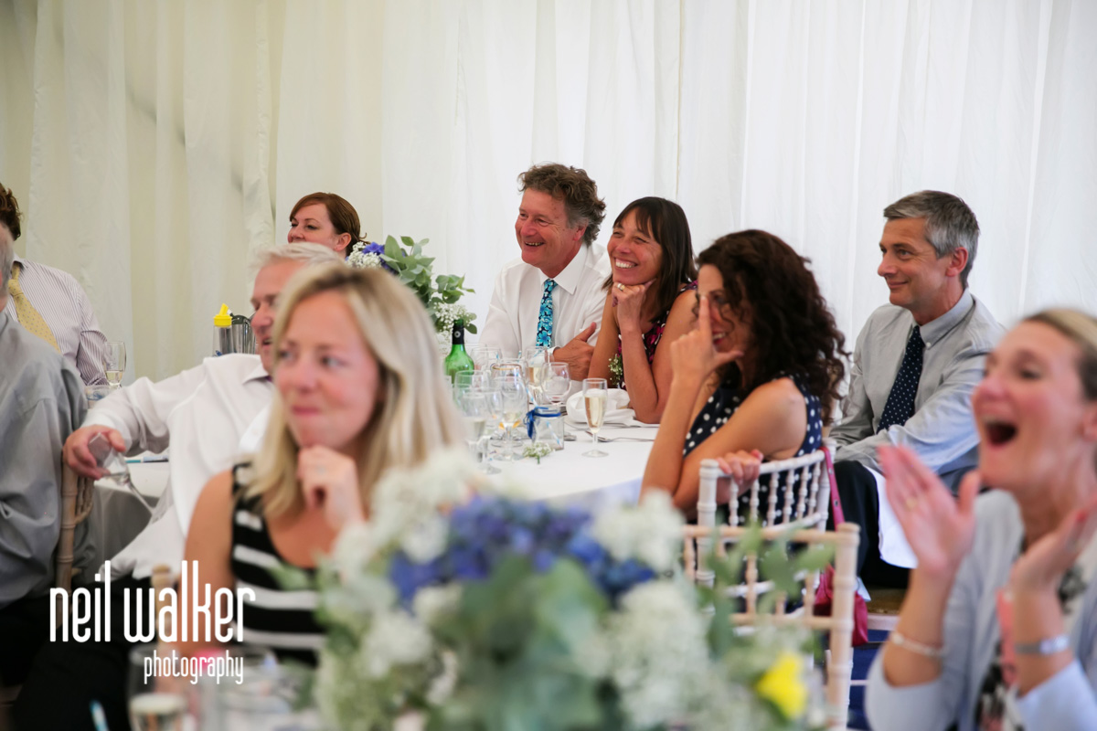 guests laughing at the best man's speech