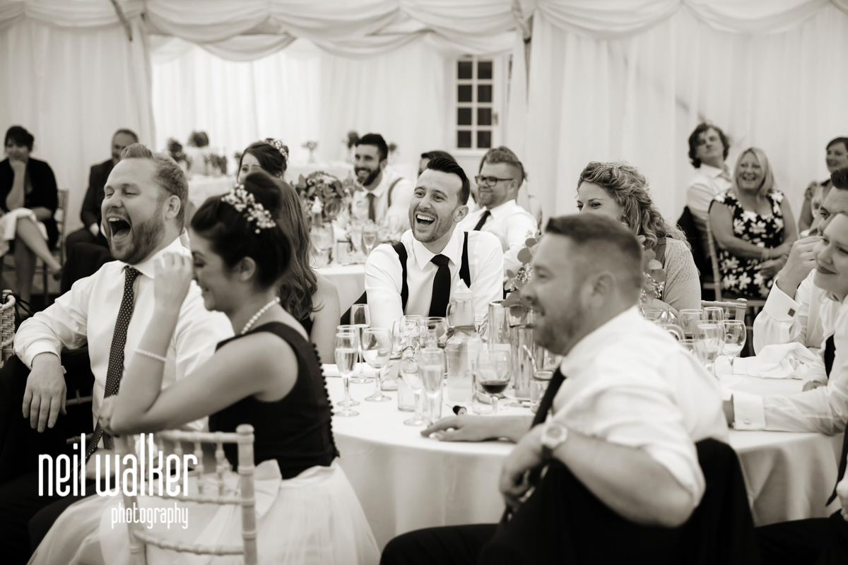 brother of bride laughing at best man's speech