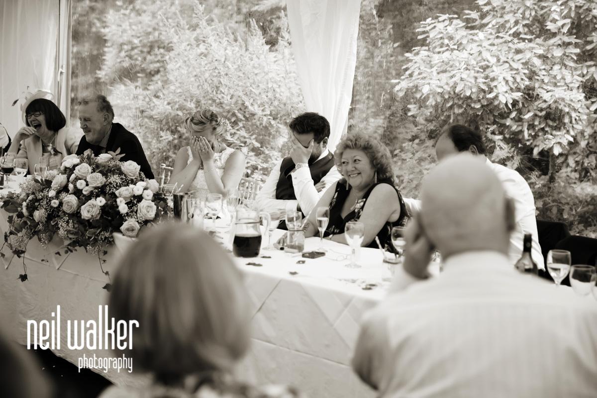 bride & groom put their heads in their hands as best man speaks