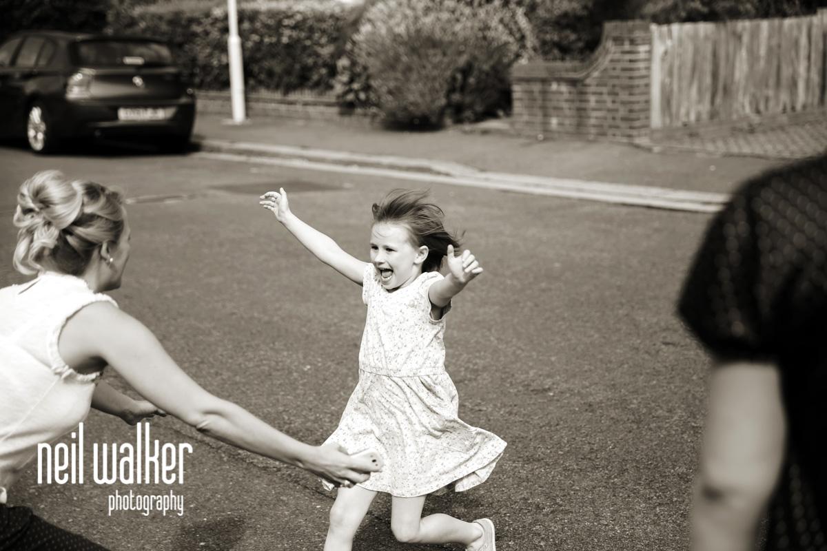 a flower girl running to hug a bridesmaid