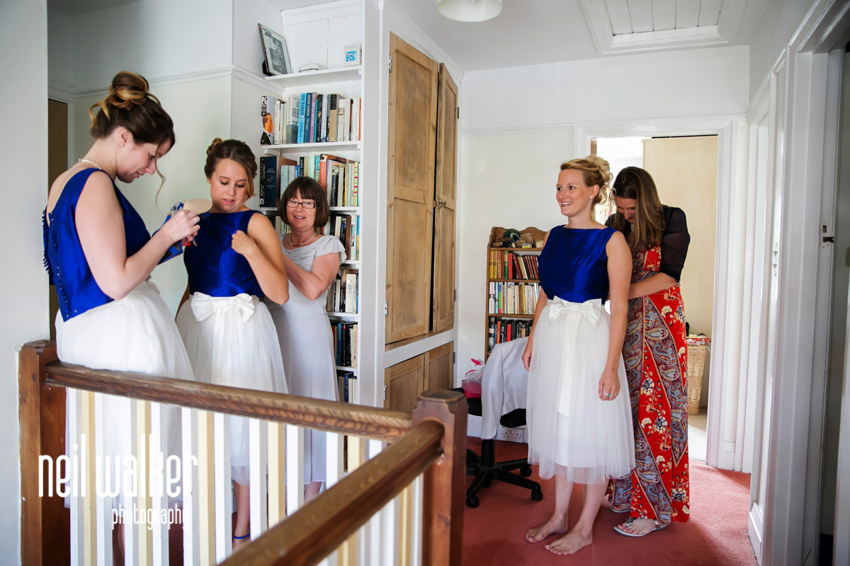 the bridesmaids putting on their dresses