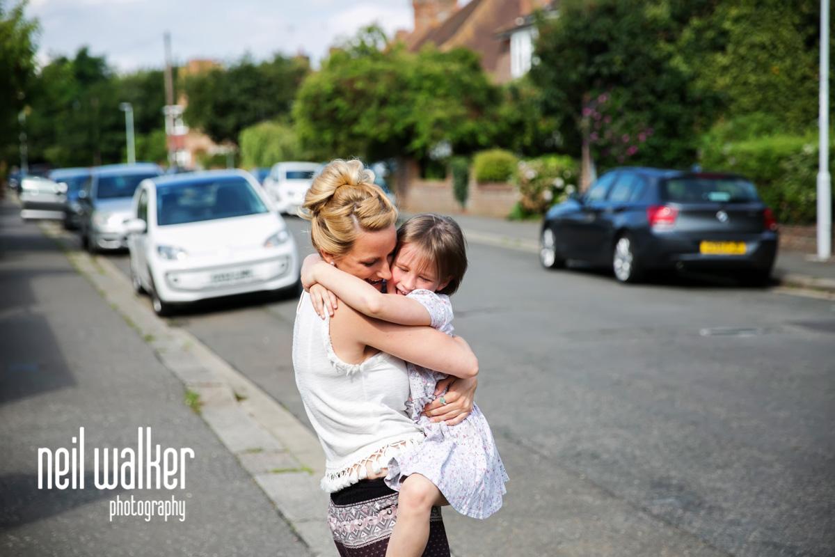 flower girl hugging a bridesmaid