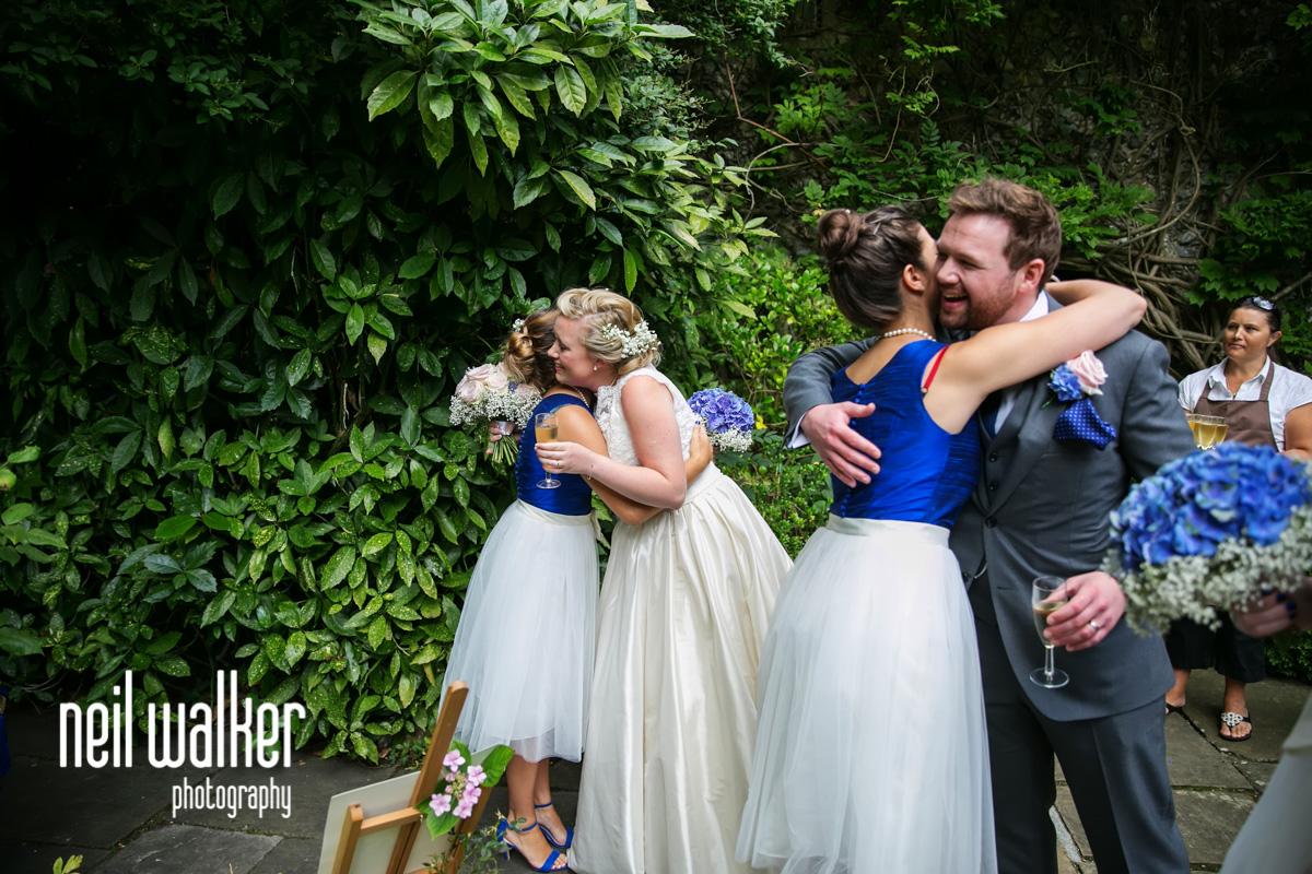 bridesmaids hugging the bride & groom