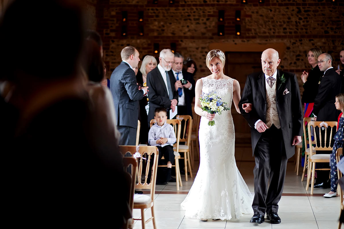 the bride walking down the aisle at Upwaltham Barns to her husband to be