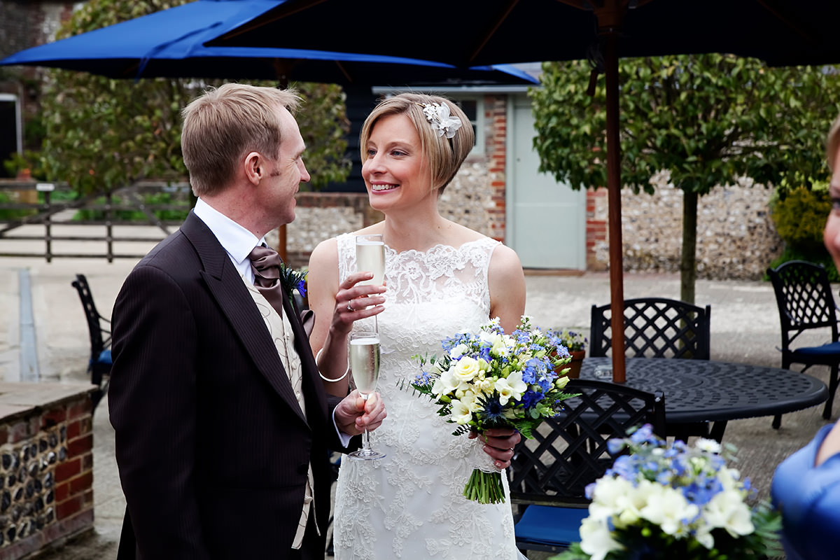 a bride & groom in the courtyard at Upwaltham Barns