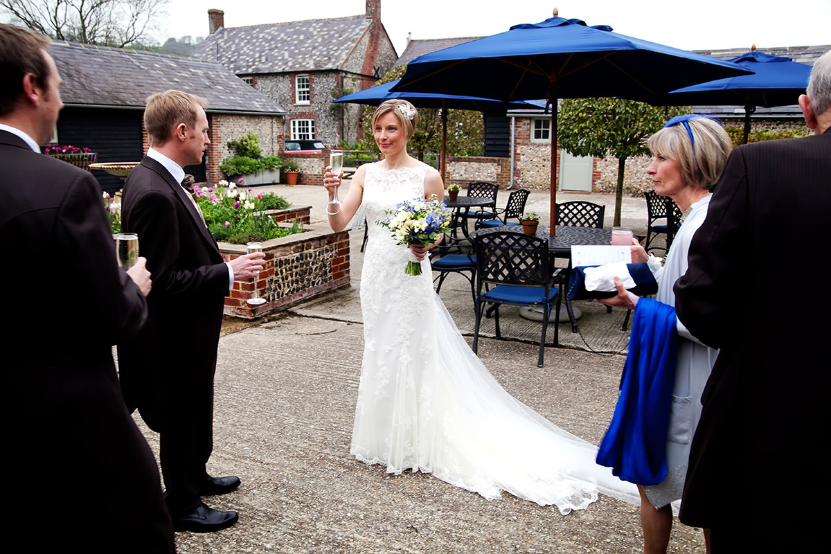 a bride being admired in the courtyard at Upwaltham Barns
