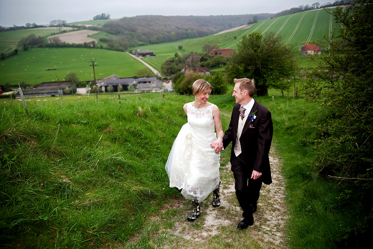 the bride & groom walking on the South Downs above Upwaltham Barns