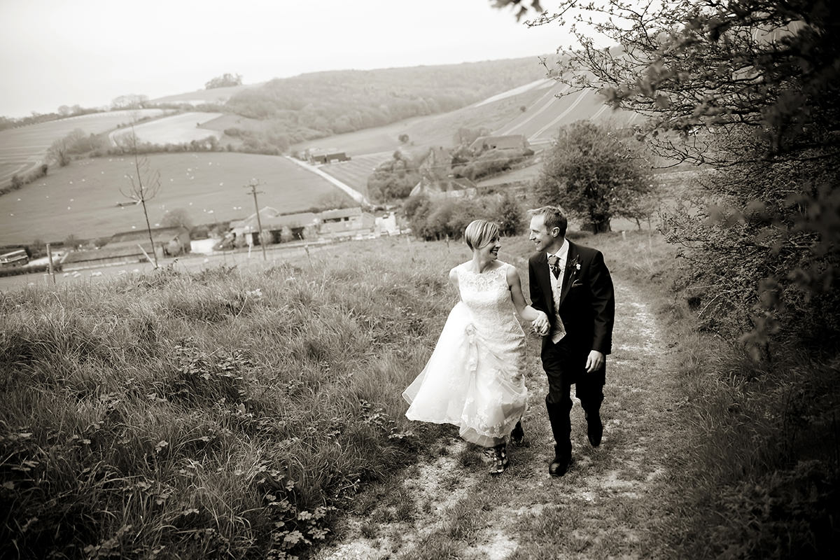 the bride & groom walking together above Upwaltham Barns