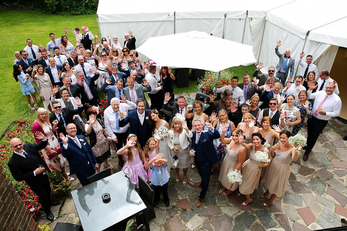 a big group shot of everyone at a wedding at Findon Manor
