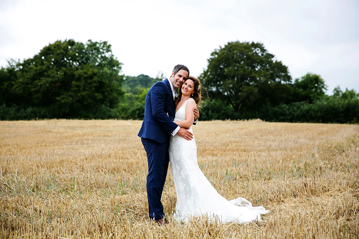 the bride & groom posing for a photo in a field of wheat at their Findon Manor wedding