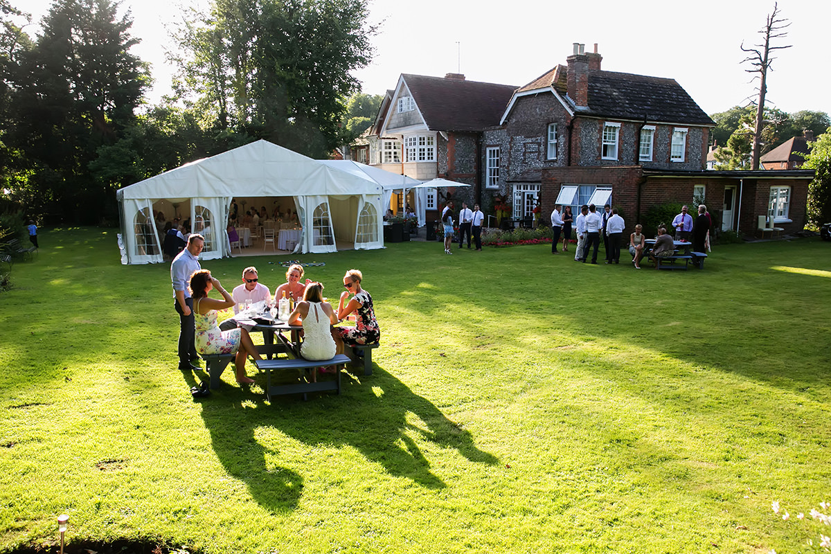 guests enjoying themselves in the garden at Findon Manor during a wedding