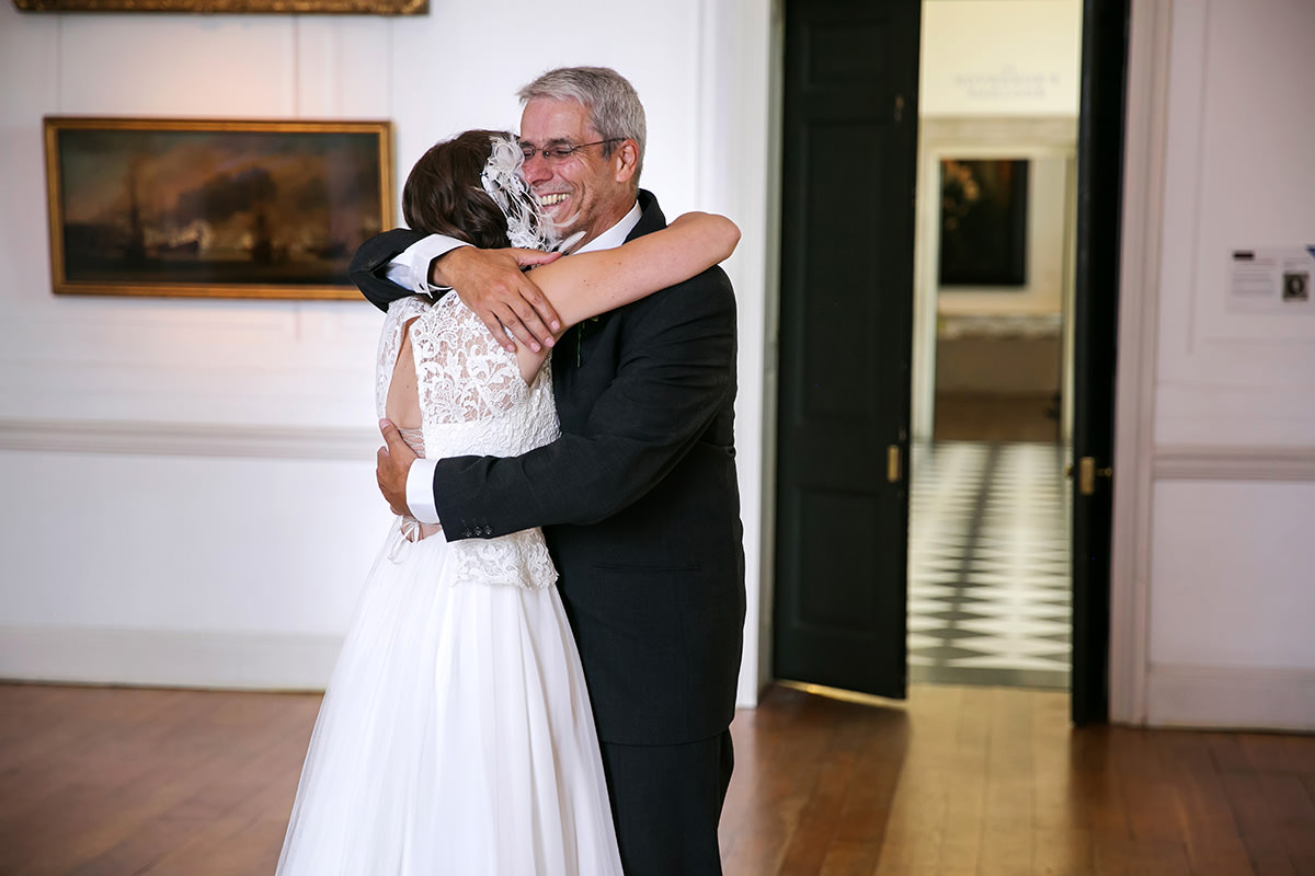 a father & the bride hug before the wedding ceremony