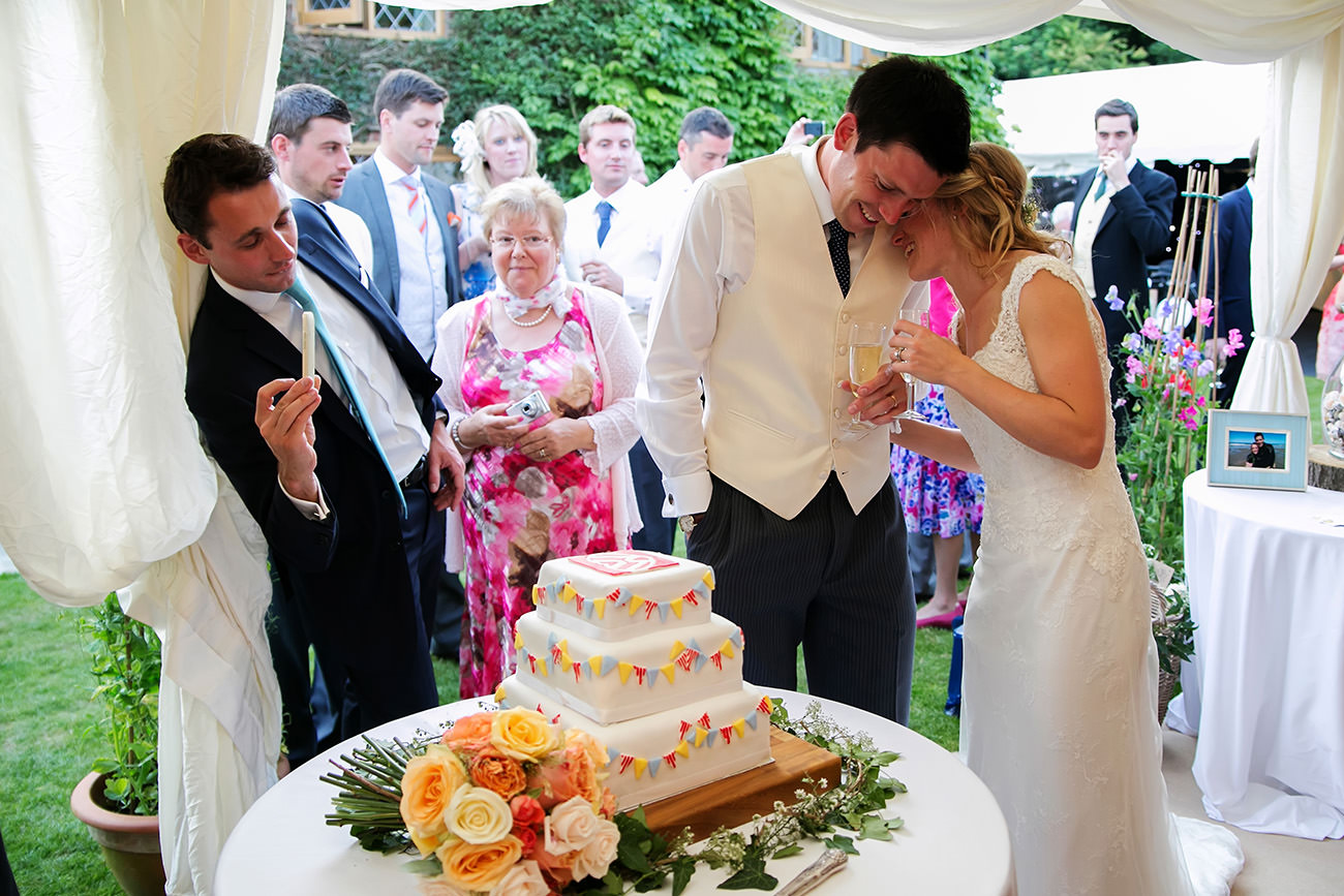 a bride & groom cutting their cake on their wedding day in Sussex