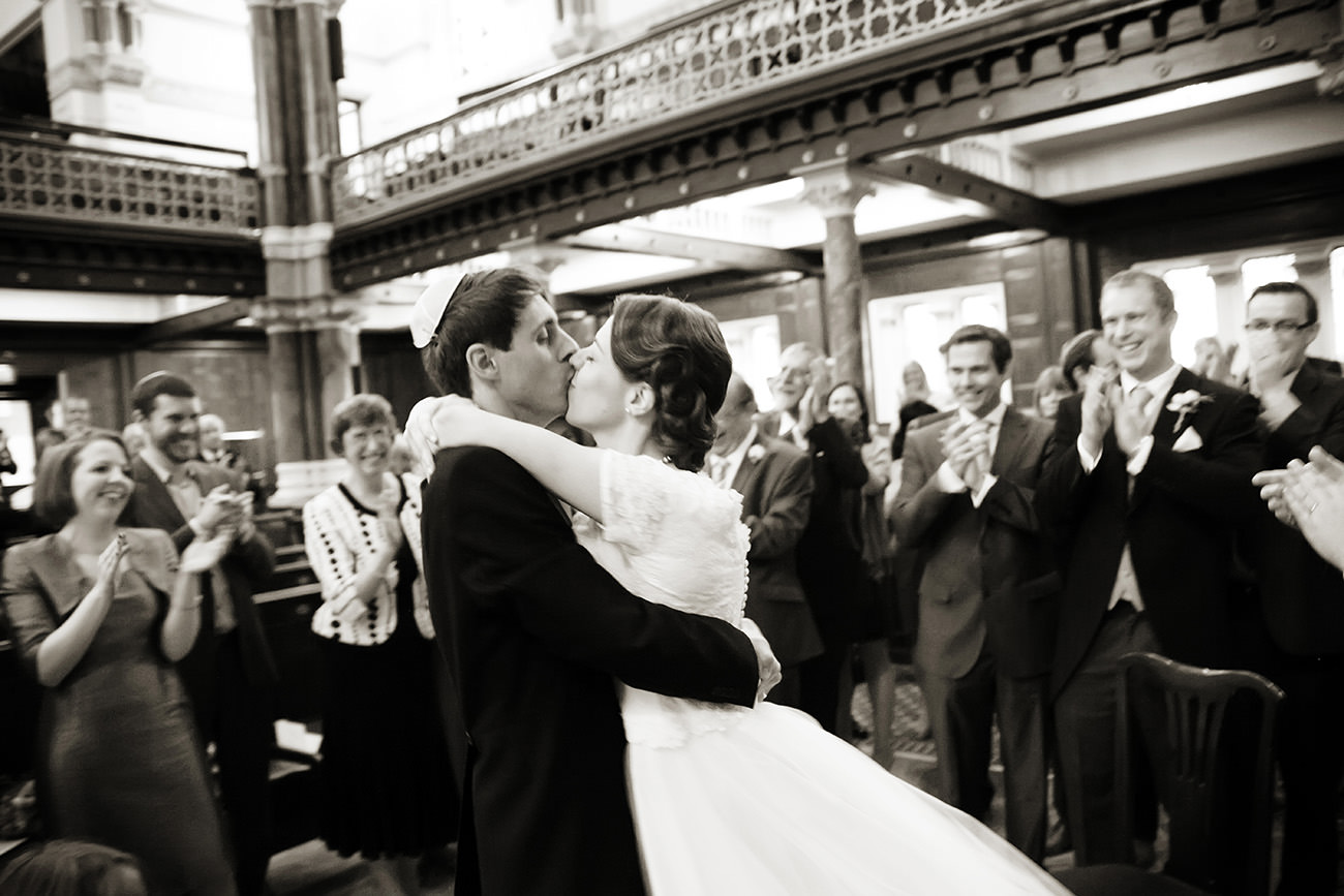 a groom kissing his bride at a Jewish wedding ceremony