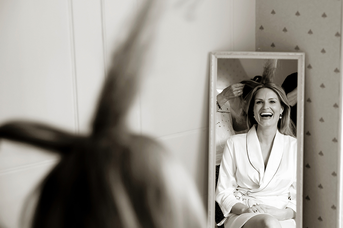 a bride laughing while having her hair styled for her wedding