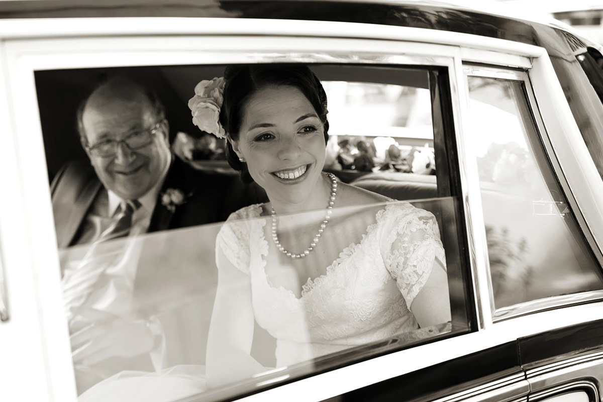 a bride in the wedding car with her father