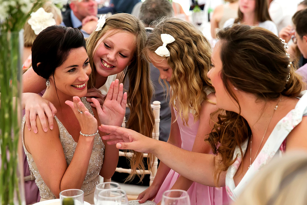 a bridesmaid laughing with the flower girls & a guest