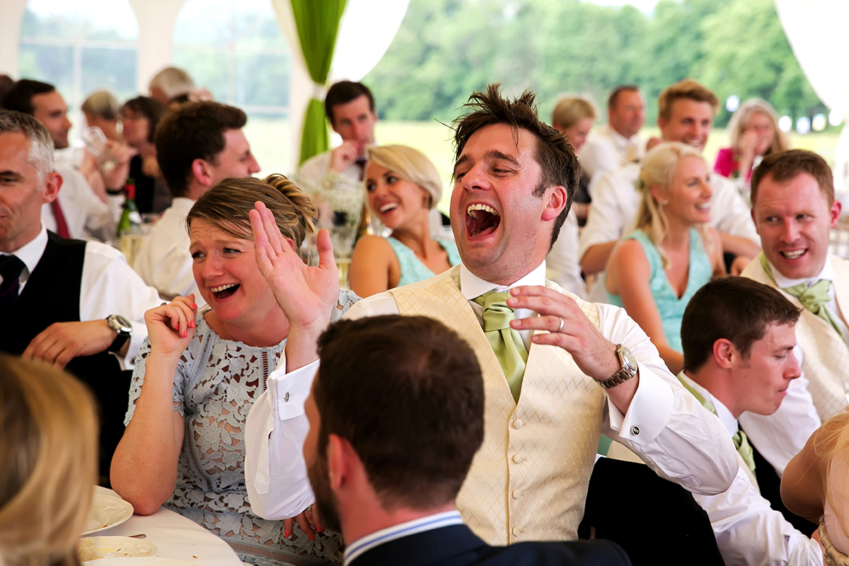 a guest laughing at the best man's speech at a wedding
