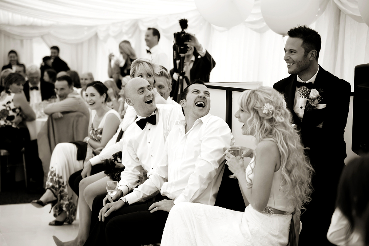 wedding guests laughing at the best man's speech