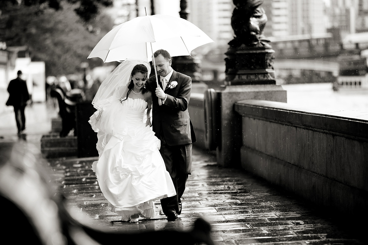 a bride & groom under an umbrella on a rainy wedding day in London