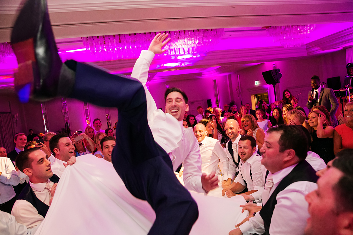 a groom being thrown in the air with a sheet during Jewish wedding celebrations