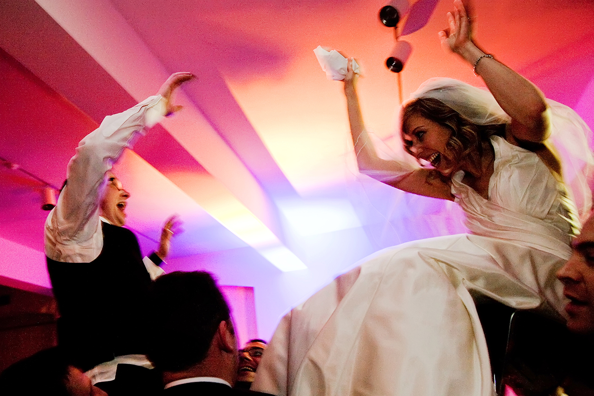 a bride & bridesmaid being carried on chairs above the guests at a Jewish wedding