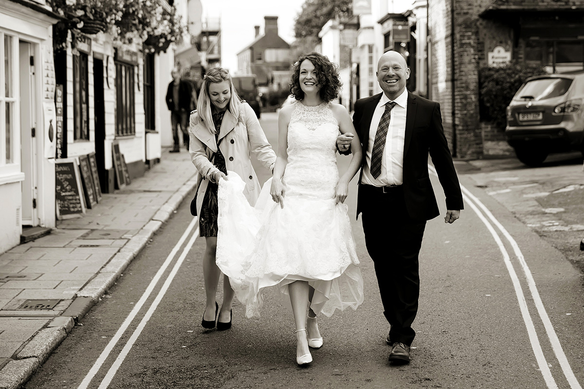a bride with her father & a bridesmaid walking to their wedding