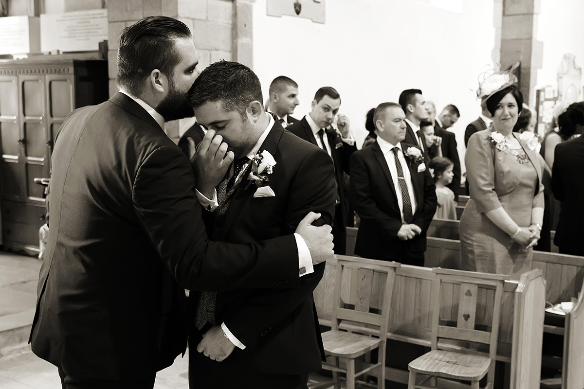 a groom waiting for his bride, being comforted by his best man
