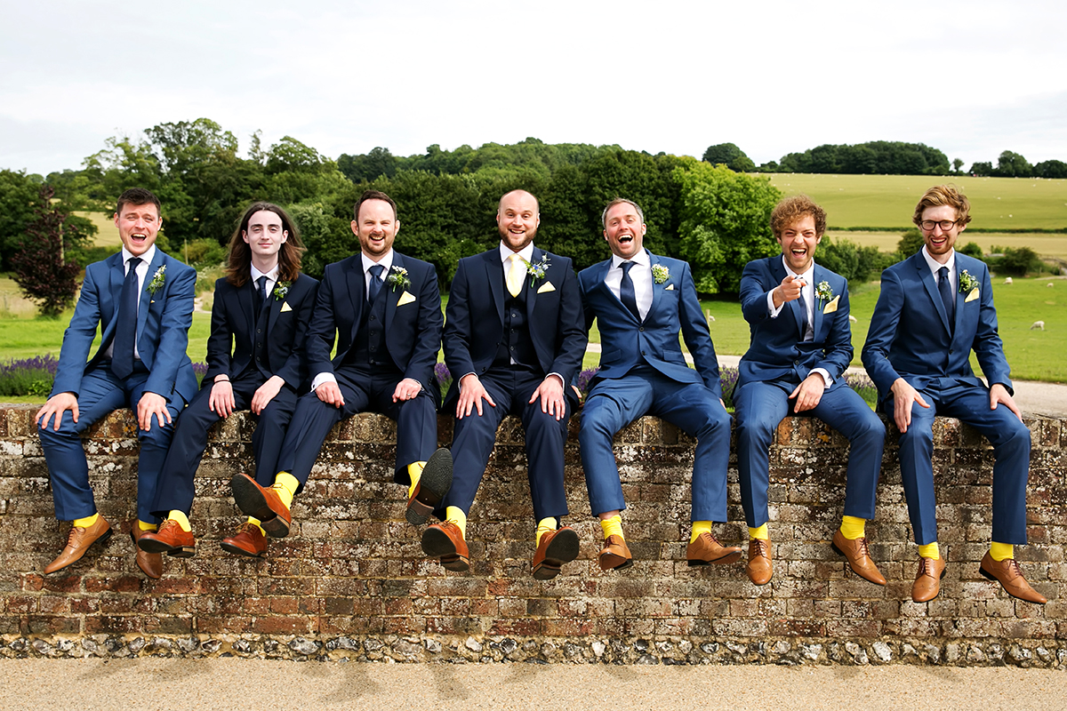groomsmen sitting on a wall