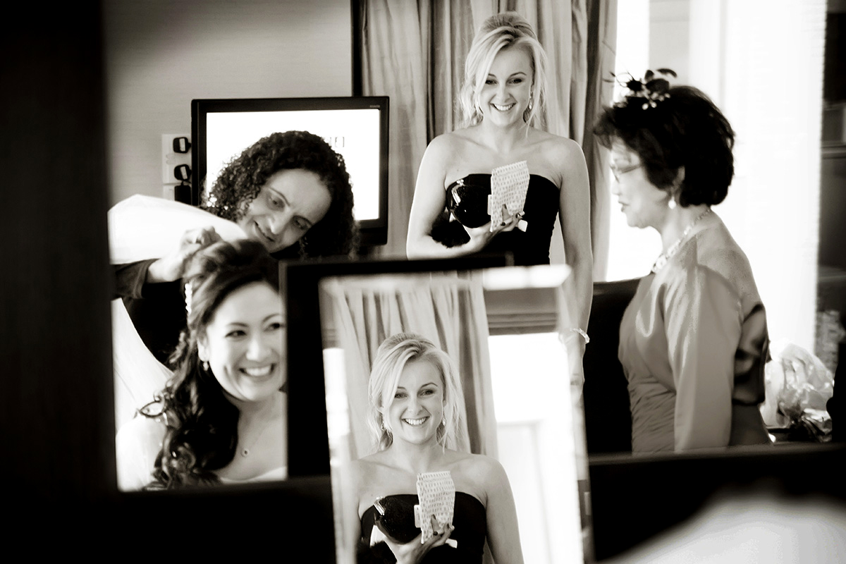 reflections in a mirror of the bride & her bridesmaids getting ready