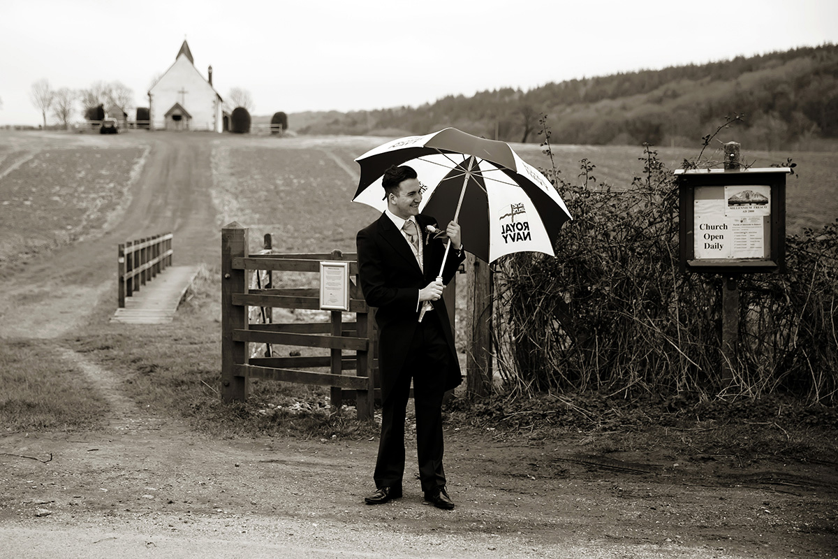 a groomsman waiting with an umbrella for the bride to arrive