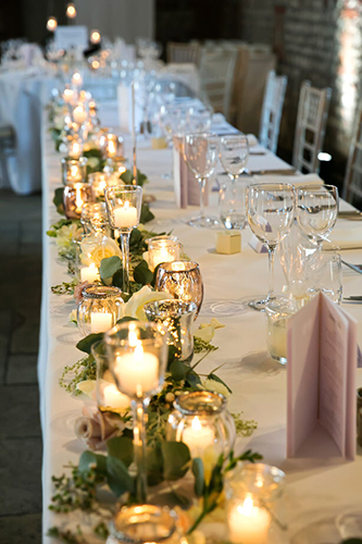 candles on the top table at a wedding