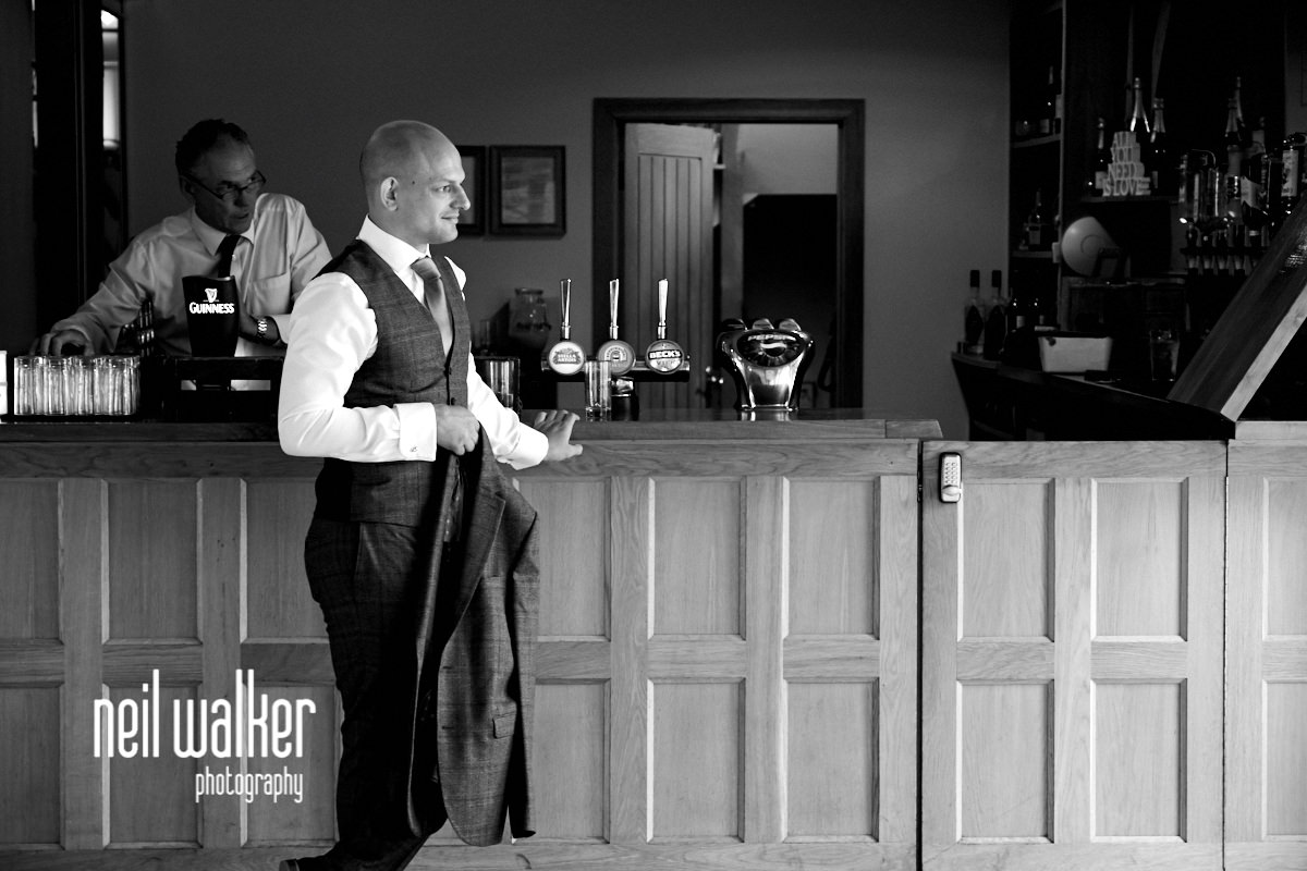 the groom standing by the bar