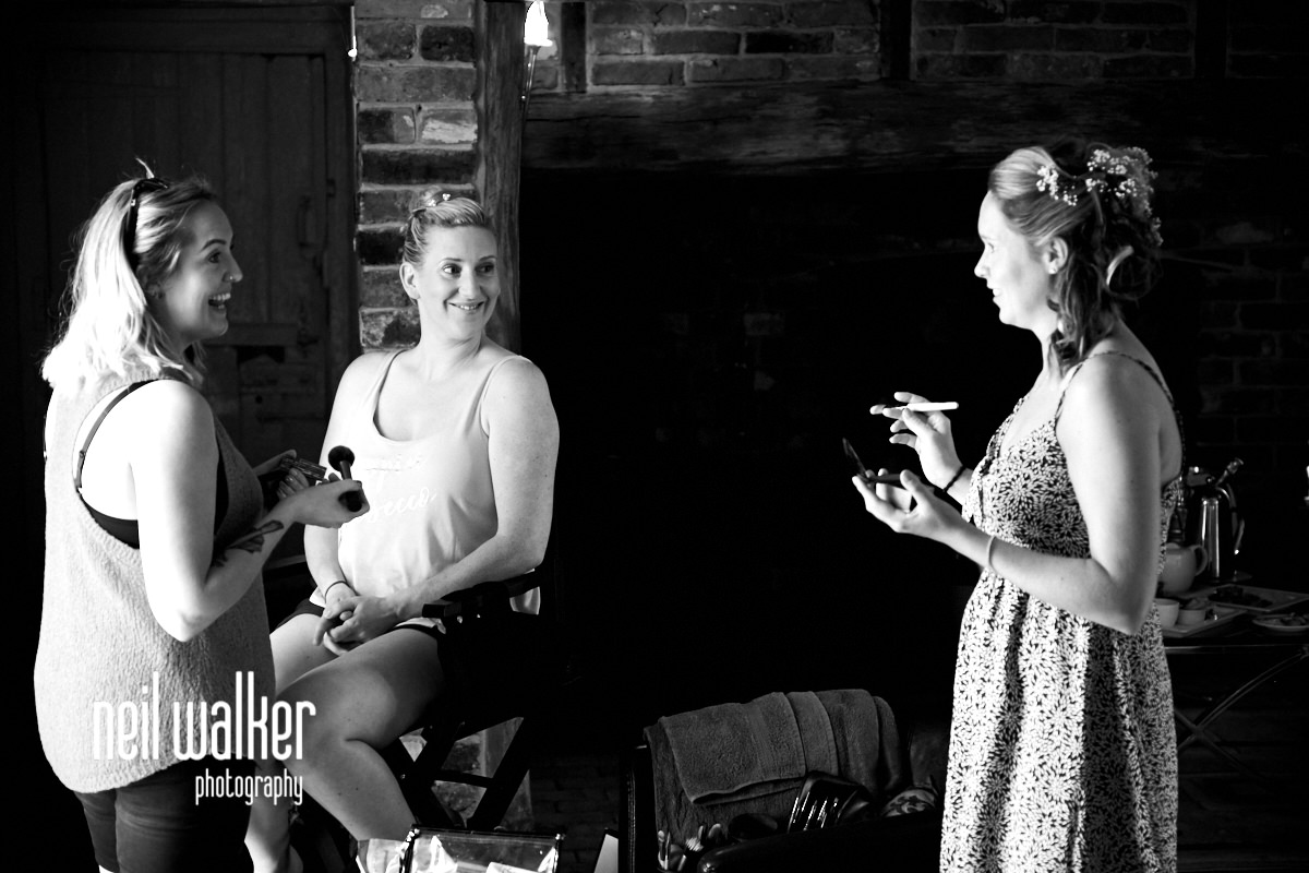 the bride laughing with her bridesmaids while she is having makeup put on