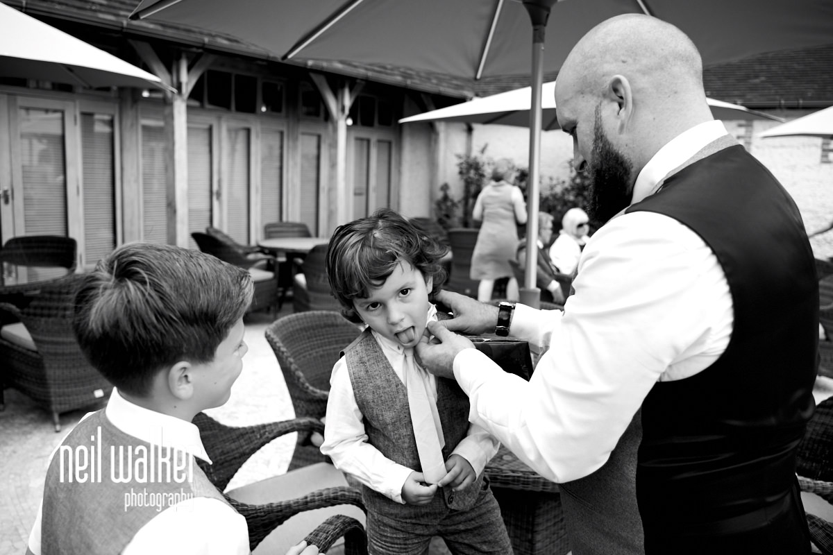 a page boy having his tie done up