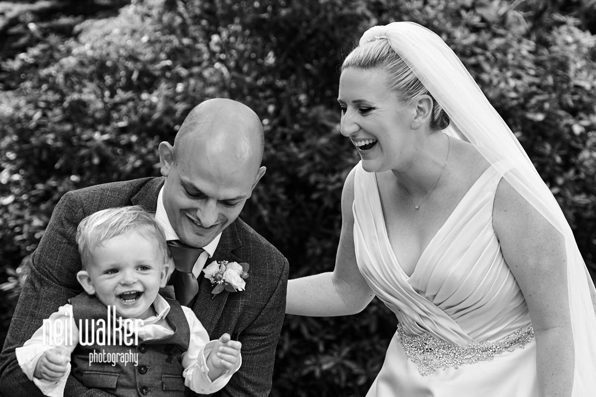 the bride & groom & their son laughing together