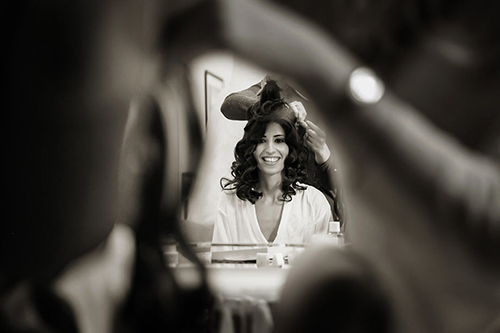 a bride having her hair & makeup done before the ceremony