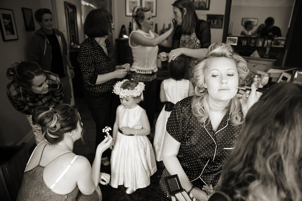a bride having her makeup done while everyone gets ready behind her