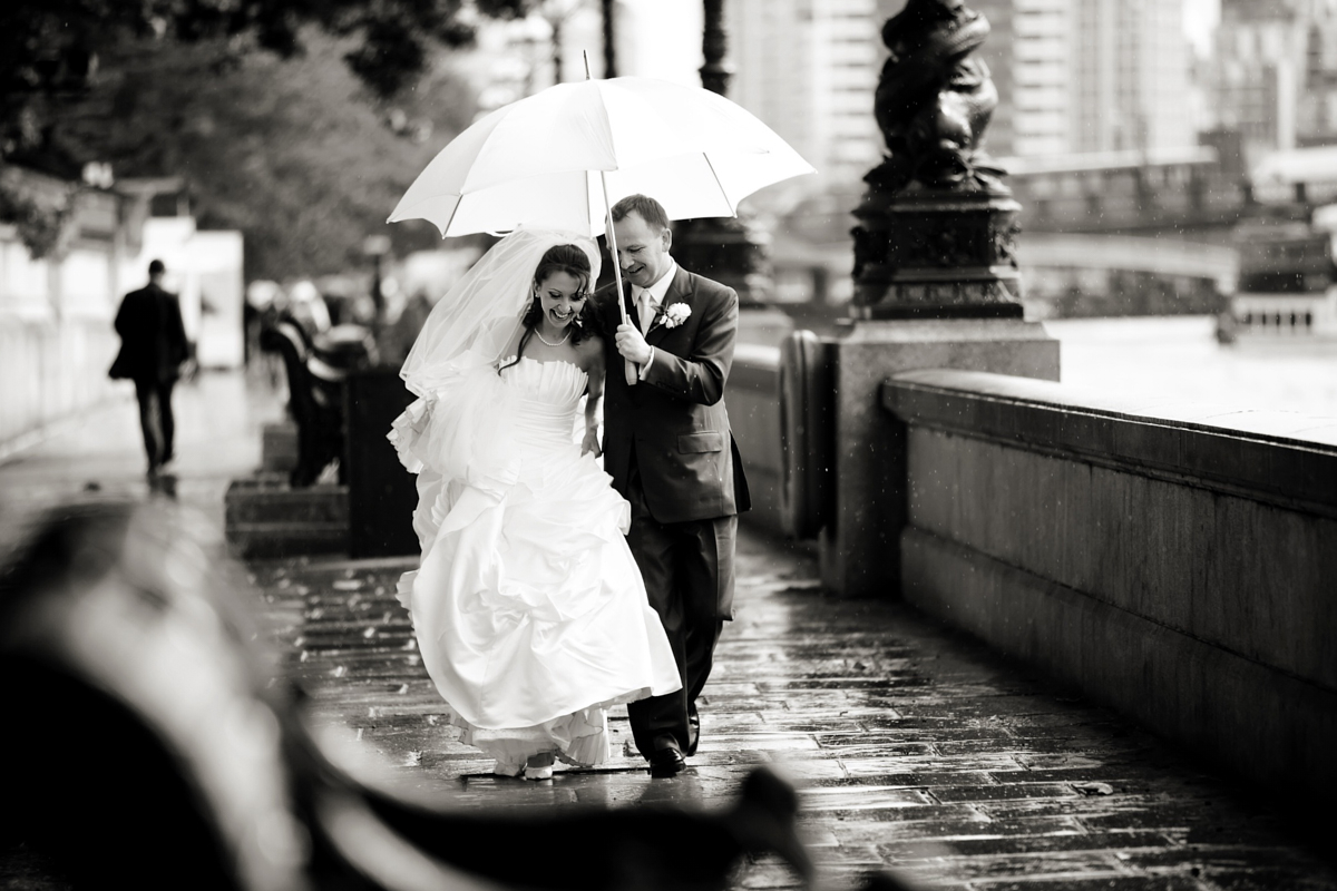 a bride and groom under a white umbrella on a rainy wedding day