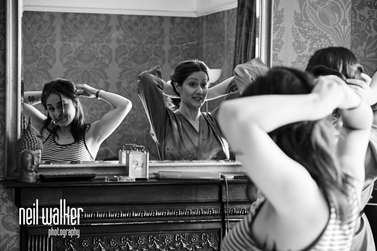 the bride and bridesmaid doing their hair in the mirror