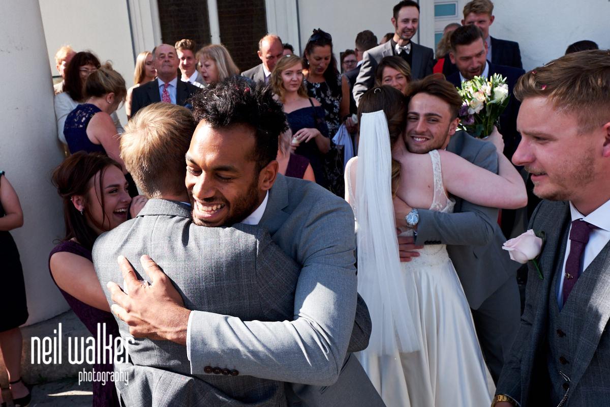 an usher hugging the groom