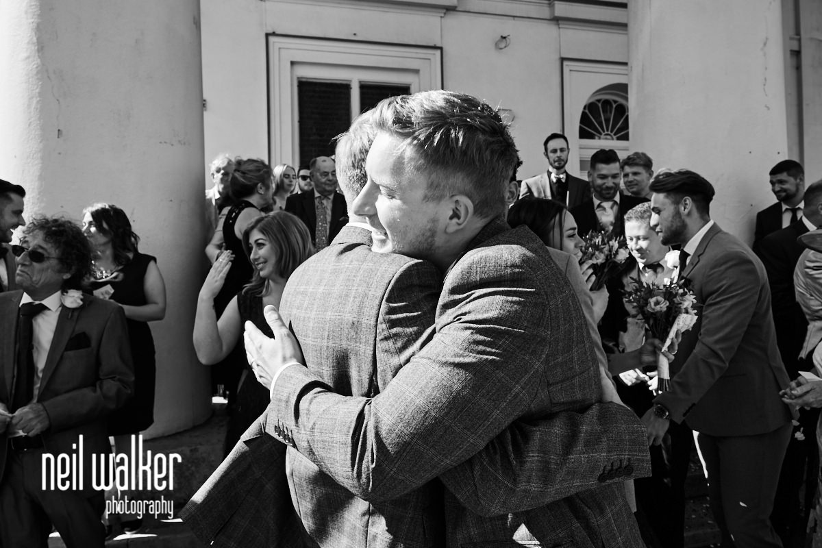 the best man hugging the groom