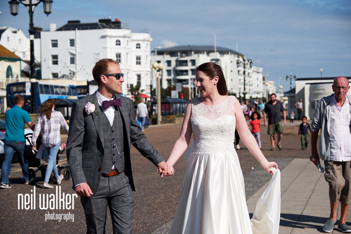 the bride and groom walking together in the sunshine
