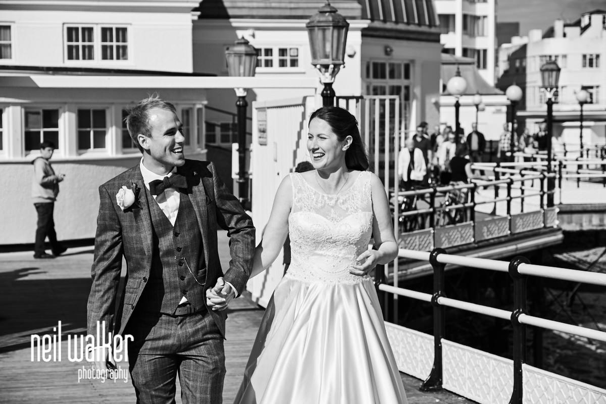 the bride and groom walking together on Worthing Pier