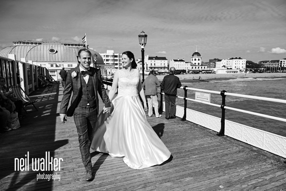 the bride and groom smiling as they walk on Worthing Pier