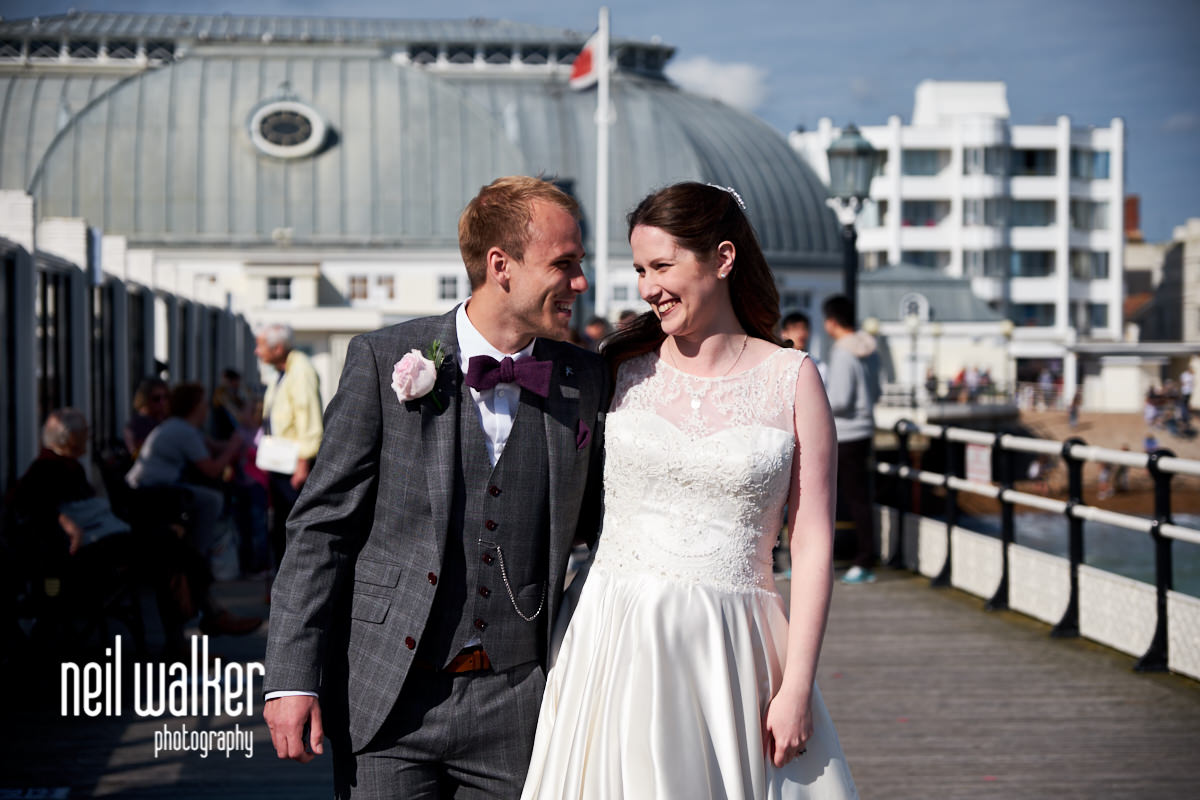 the bride and groom smiling at each other on Worthing Pier