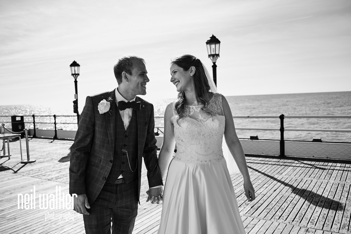 the bride and groom together on Worthing Pier