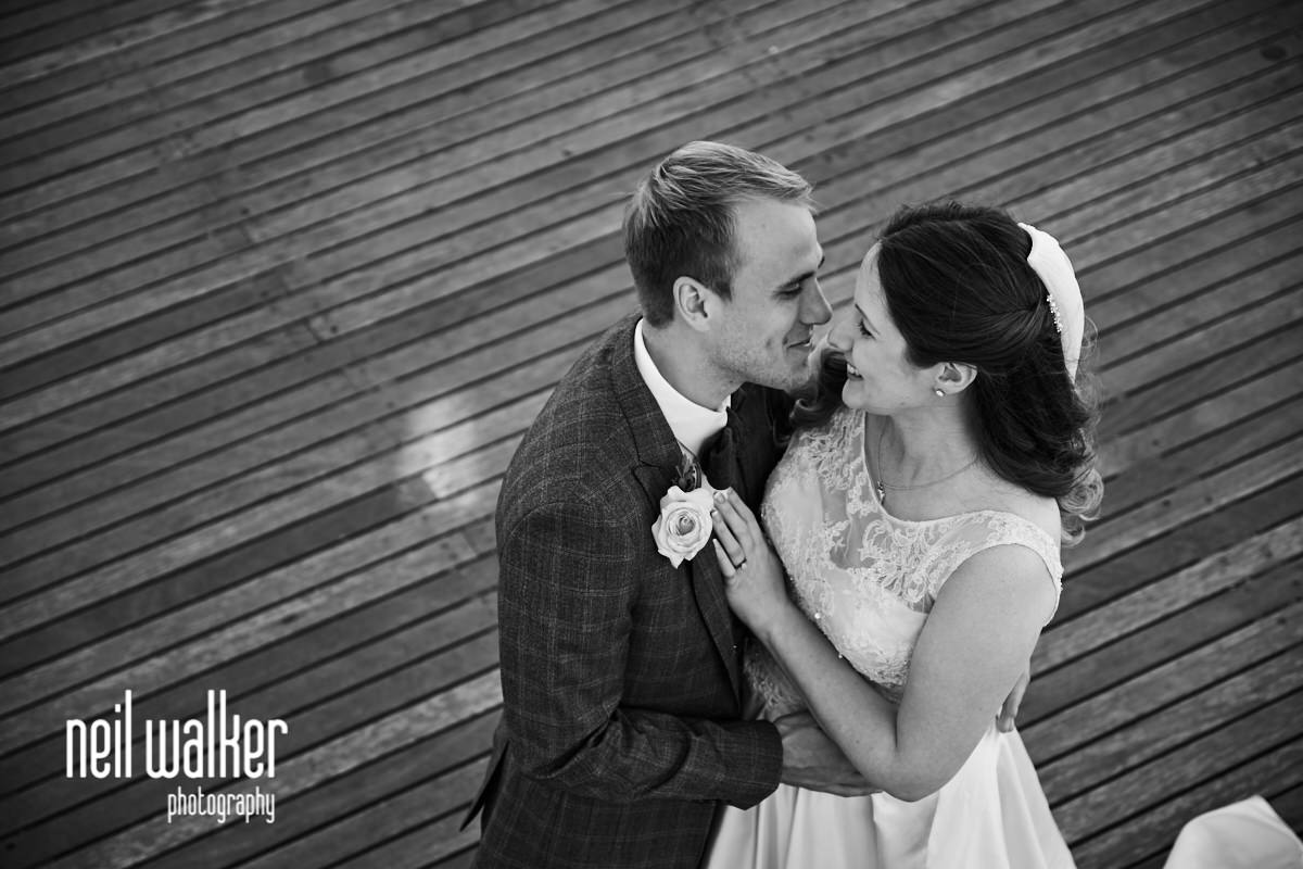 the bride and groom hugging on Worthing Pier